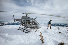 Helicopter Pilot Explores A Snow-covered Mountain Summit.