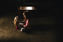 Girl Playing With Doll In Living Room At Home