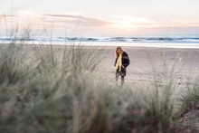 Preteen Girl In Coat And Scarf Looking Down At A Beach At Dawn