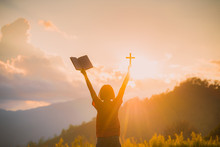 The Silhouette Of A Woman's Hand, Praying Spiritually Over The Sun, Shining With A Beautiful Blurred Sunset Backdrop. Is A Belief In The Christian Concept: