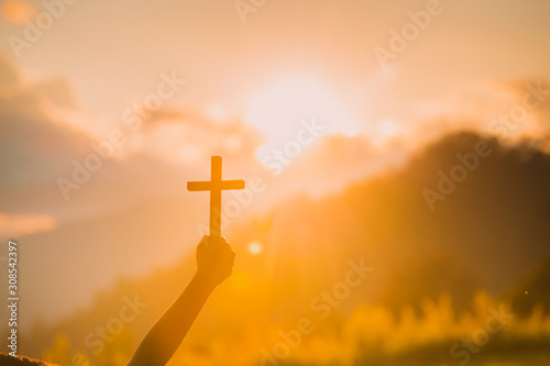 The silhouette of a woman's hand, praying spiritually over the sun, shining with a beautiful blurred sunset backdrop Wallpaper Mural