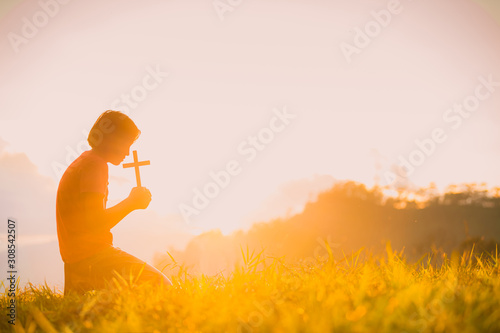Photo The silhouette of a woman's hand, praying spiritually over the sun, shining with a beautiful blurred sunset backdrop