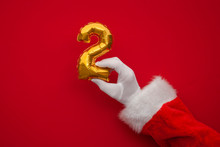 12 Days Of Christmas. Santa Hands Holding 2nd Day Balloon On Red Background