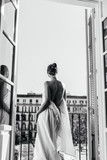 Fototapeta Fototapety Paryż - A girl resting at the hotel stands in the opening of an open balcony, wrapped in a sheet. The naked back is turned to the camera, photo black and white