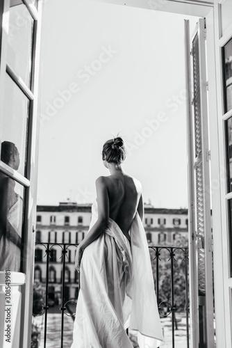 Dziewczyna odpoczywająca w hotelu stoi w otworze otwartego balkonu, owinięta w prześcieradło. Nagie plecy zwrócone do aparatu, zdjęcie czarno-białe