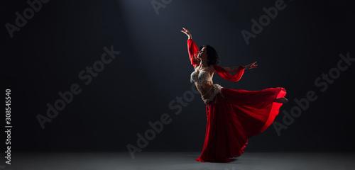Woman in red arabic dress dancing oriental dances arabesque pose