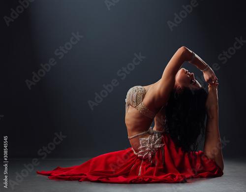 Obraz beautiful black-haired girl in red ethnic dress dancing oriental dances leaning back - fototapety do salonu