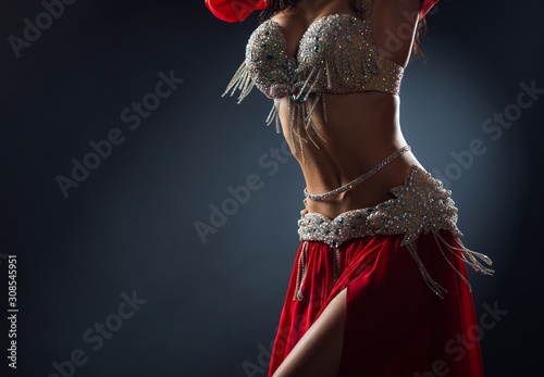 Beautiful belly dance of a girl in a red decorated ethnic dress in dark - 308545951
