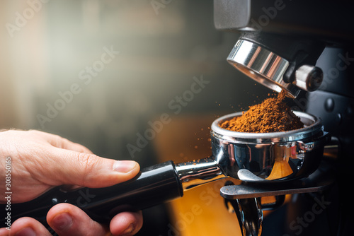 Fotografija ground coffee pouring into a portafilter with a grinder