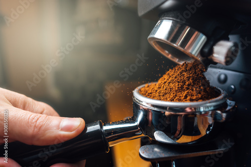 Obraz ground coffee pouring into a portafilter with a grinder - fototapety do salonu
