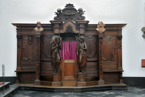 Photo A wooden confessional box with red velvet curtains in the Roman Catholic Church
