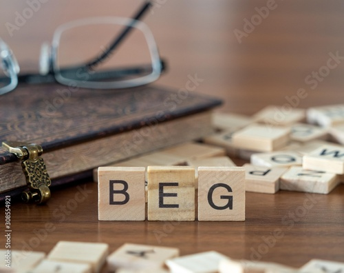 beg the word or concept represented by wooden letter tiles Canvas Print