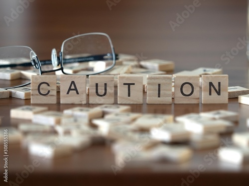 Photo caution the word or concept represented by wooden letter tiles