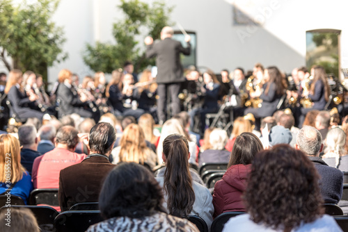 People watching a concert of classical music, blurred women and men and other people watching listening to concert of classical music on a sunny day Fototapete