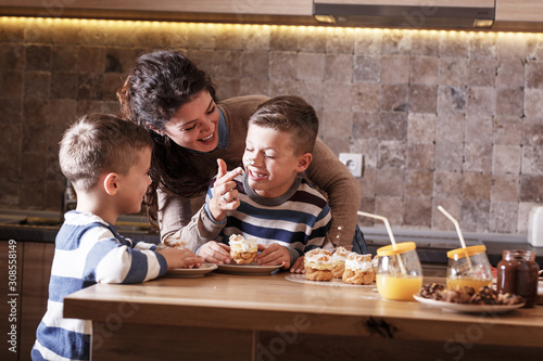 Fotografia, Obraz Mother  and her two little sons eating cakes at the kitchen