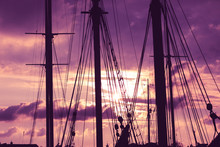 Silhouette Of Masts And Ropes Of A Wooden Old Sailing Ship Against The Background Of The Evening Dark Pink Purple Neon Magical Sky