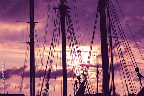 Foto auf AluDibond Schiff Silhouette of masts and ropes of a wooden old sailing ship against the background of the evening dark pink purple neon magical sky