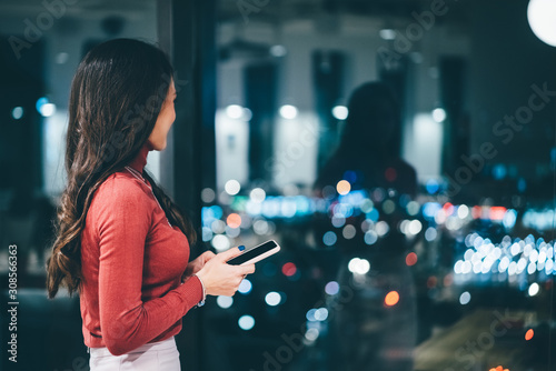 Obraz Portrait of young worker using phone, looking out the window at her workplace in evening. - fototapety do salonu