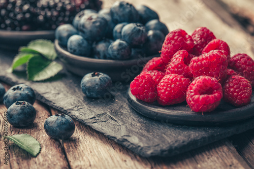 Fototapeta Fresh berries with raspberries, blueberries, blackberries in bowl on a stone stand on wood background. obraz