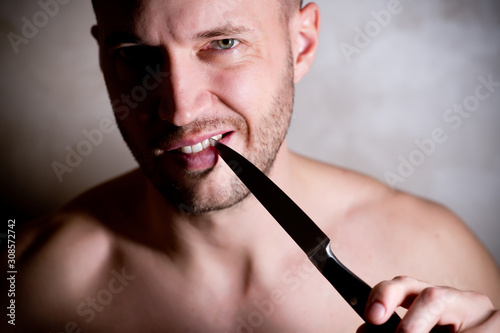 Fotografia, Obraz man cleans the space between his teeth with a knife