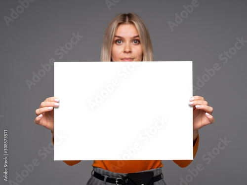 Gorgeous young woman holding a mockup vertical A1 white paper sheet with copy sp Canvas Print