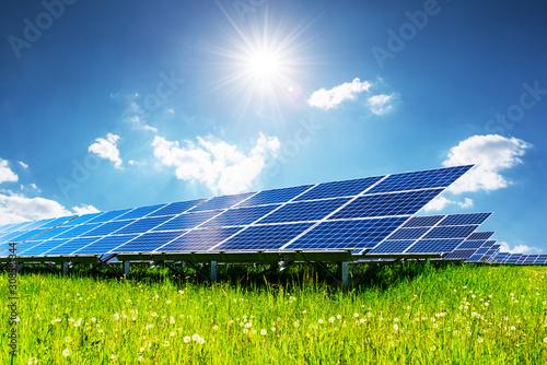 Fototapeta Solar panel under blue sky with sun. Green grass and cloudy sky. Alternative energy concept obraz