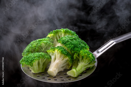Fresh broccoli on a spoon scoop, ready for use by vegetarians. in steam