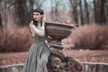 Fabulous Brunette Model In Dress. Gothic Model Sitting On Old Fountain. Victorian Outfit. Brunette Woman With Bang. Model In Dress On Autumn Background. Vintage Fountain In Park. Fashion Clothes
