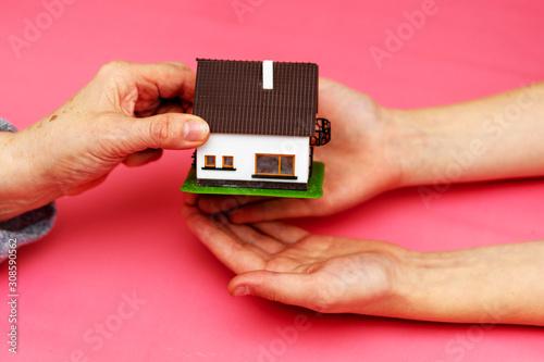 Photo Schenkung eines Einfamilienhauses symbolisiert durch das Überreichen eines Spiel