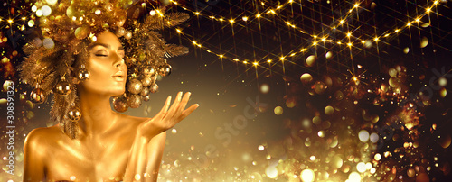 Christmas golden Woman. Winter girl pointing Hand, blowing blinking stars,  Beautiful New Year, Christmas Tree Holiday Hairstyle and gold skin Makeup. Gift. Girl in decorated Xmas wreath. Beauty Model - 308591323