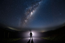 A Mysterious Man Standing In The Middle Of The Road Looking Into Bright Light With Milky Way Starry Night Sky.