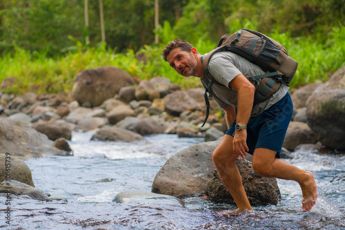 Fototapeta young happy and attractive man with travel backpack hiking in river at forest feeling free enjoying nature and fresh environment on summer trekking journey obraz