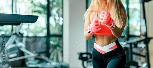 Cropped portrait of sexy fit blonde in stylish sportswear and kickboxing gloves getting ready for training Canvas Print