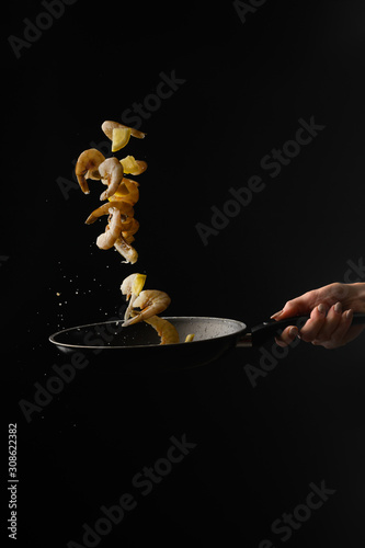 Photo Thai cuisine, the chef cooks shrimps with lemon, frying in a pan