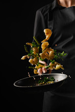 Chef Cooks Seafood, Fry Shrimps. Freezing In Motion On A Black Photo, Vertical Photo