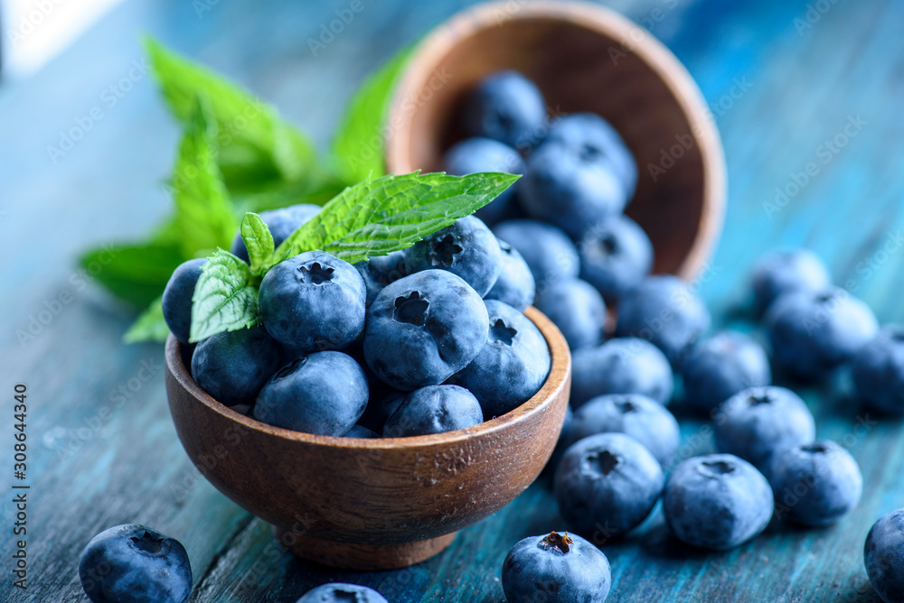 Fototapeta Bowl of fresh blueberries on blue rustic wooden table closeup.