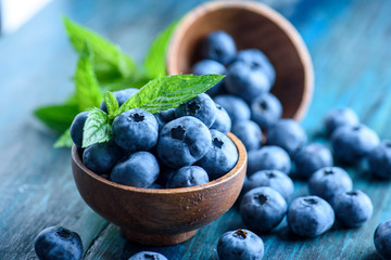 Bowl of fresh blueberries on blue rustic wooden table closeup.