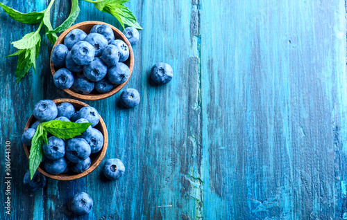 Slika na platnu Bowl of fresh blueberries on blue rustic wooden table from above.