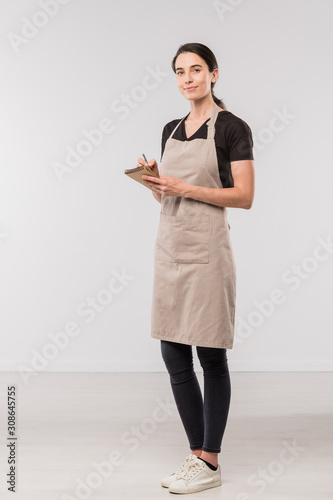 Photographie Pretty waitress in apron, black skinny jeans and t-shirt making notes in notepad