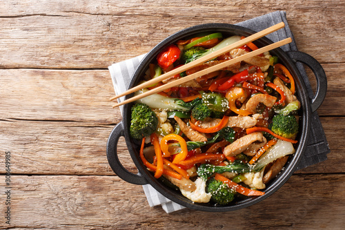 Chinese cuisine stir fry pork with vegetables and sesame seeds close-up in a pan Canvas Print