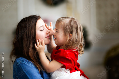 Fototapeta Tender girl with down syndrome and sister teenager obraz