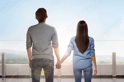 Fotomural  Rear view of Asian couple standing and holding hands each other
