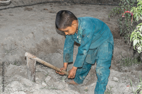 Photo a very young orphan child is forced into child labor and working at a constructi