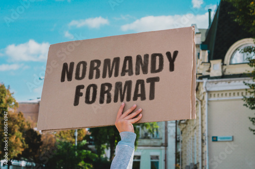 The phrase  Normandy Format  on a carton banner in men's hand Canvas Print