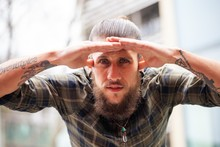 Young Man With Beard And Gauged Pierced Ears With Looking With Hand Shielding Sun