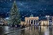 Das Brandenburger Tor in Berlin, Deutschland,  mit Weihnachtsbaum bei Nacht und Schneefall