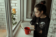 A Girl Sits By The Window And Reads A Book. Nearby Are Yellow Roses And A Red Cup.