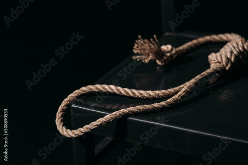 Fotografija rope noose on chair on black background, suicide prevention concept