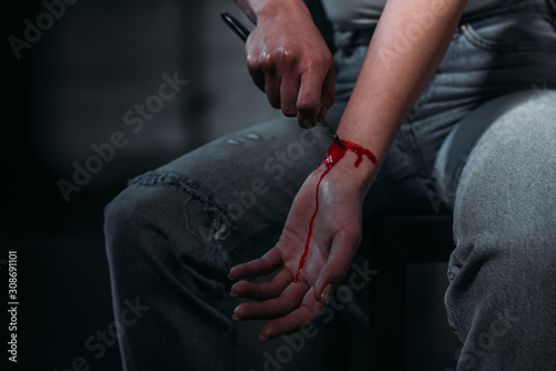 Canvas Print partial view of woman committing suicide by cutting veins with straight razor on