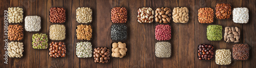 Fotografía word nuts lined with various nuts in bowls on wooden table.